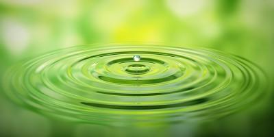Wassertropfen auf Wasser mit grner Spiegelung